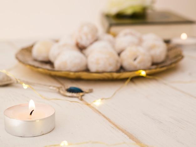 Plato de galletas desenfocado con vela y corán.