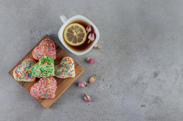 Un plato de galletas en forma de corazón con chispitas sobre una piedra