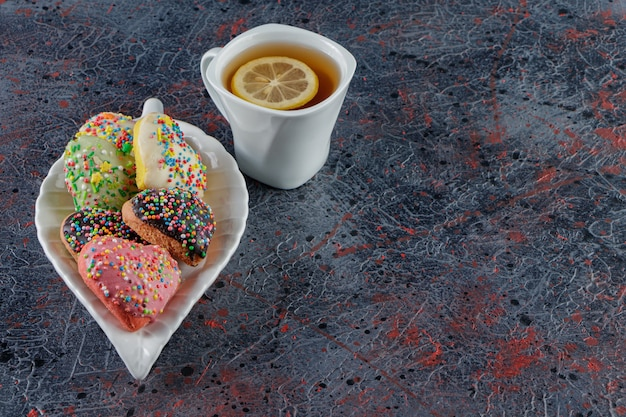 Un plato de galletas en forma de corazón con chispitas y una taza de té caliente