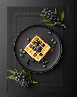 Plato de gofres con uvas sobre un paño oscuro