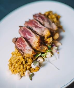 Plato gourmet de delicados cortes de ternera sobre un exquisito arroz especiado