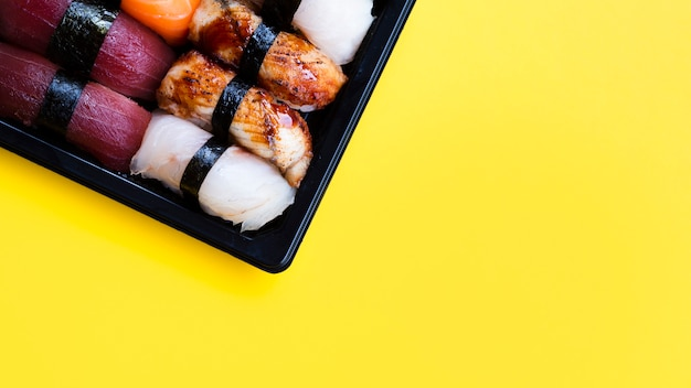 Plato grande de sushi negro sobre un fondo amarillo