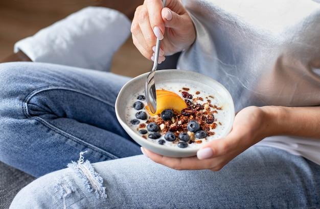 Plato con granola y bayas frescas en manos de una joven