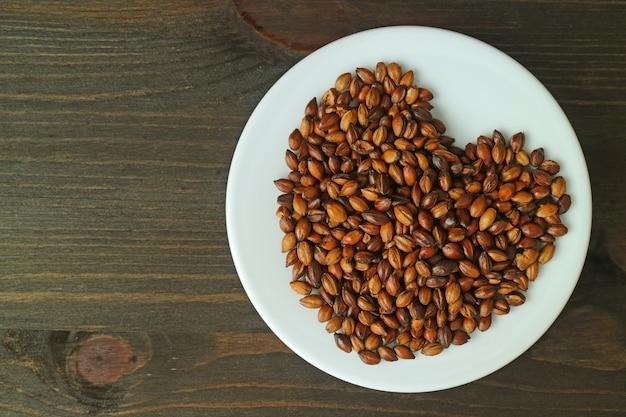 Plato de granos de cebada asada en mesa de madera