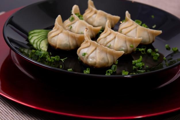 Plato de gyoza de comida japonesa, dim sum, comida fresca asiática con verduras en un plato negro