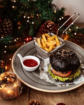 Un plato de hamburguesa de ternera negra servido con papas fritas y salsa de tomate