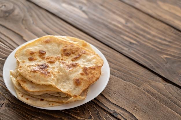 En un plato hay pasteles de pan frito, mesa de madera con textura. con texto libre, copia espacio,
