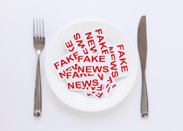 Plato con hojas de papel con fake news