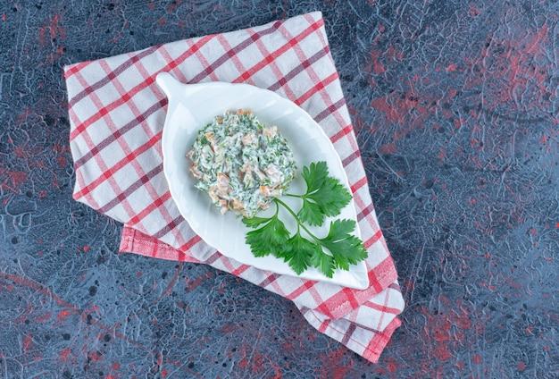Un plato hondo blanco con deliciosa ensalada y hierbas.