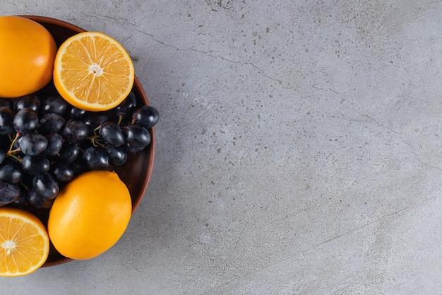 Plato hondo de uvas negras frescas y naranjas sobre mesa de piedra.