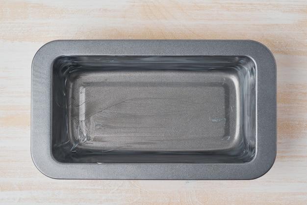 Plato para hornear engrasado con aceite, pan de molde con mantequilla. receta paso a paso para el pan de plátano.