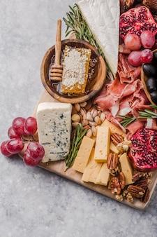 Plato italiano antipasto tradicional. surtido de quesos en tabla de cortar de madera. queso brie, rodajas de queso cheddar, gogonzola, nueces uvas, aceitunas, jamón, romero y copa de vino tinto. vista superior
