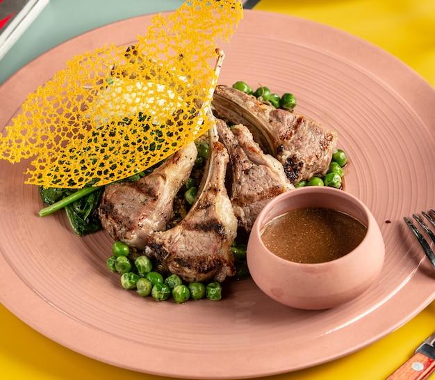 Plato de kebab de costillas de cordero servido con guisantes verdes, espinacas y salsa