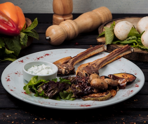 Plato de kebab de costillas de cordero servido con yogur, ensalada y verduras a la parrilla
