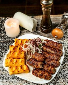 Plato de kebab de lula y patata adornado con cebolla y zumaque