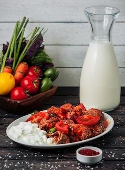 Plato de kebab de ternera con salsa de tomate, servido con yogur