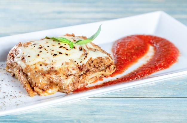 Plato de lasaña de carne tradicional con salsa de tomate