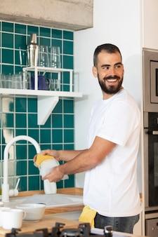 Plato de lavado de hombre sonriente de tiro medio