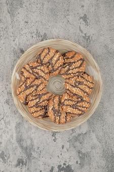 Plato lleno de galletas de avena dulce con sirope de chocolate sobre una piedra.