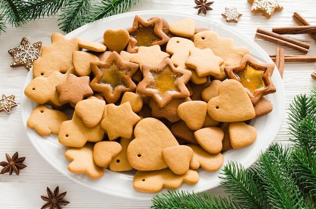 Plato lleno de pan de jengibre de navidad recién horneado en madera blanca.