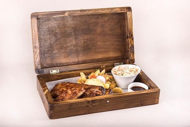 Plato de lujo con costillas de cerdo a la parrilla, salsa barbacoa, papas fritas, ensalada de col, en una caja de madera