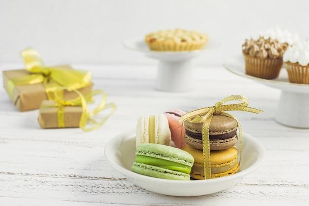 Plato de macarons con dulces borrosos detrás