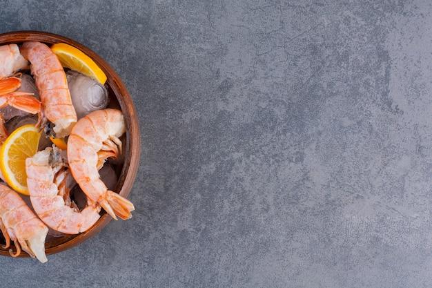 Un plato de madera de deliciosos camarones con cubitos de hielo y rodajas de limón sobre un fondo de piedra.