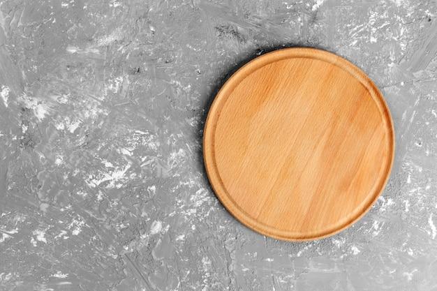 Plato de madera en el fondo con textura gris. vista superior
