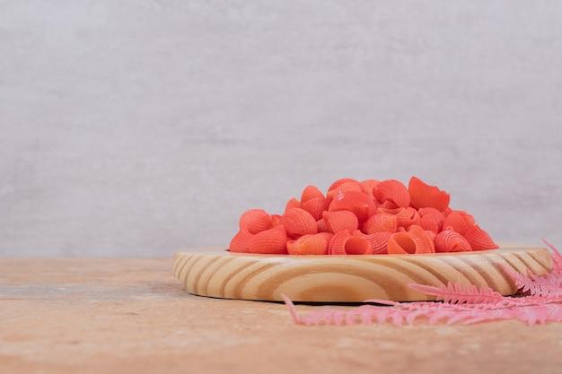 Un plato de madera lleno de macarrones rojos sin preparar. foto de alta calidad