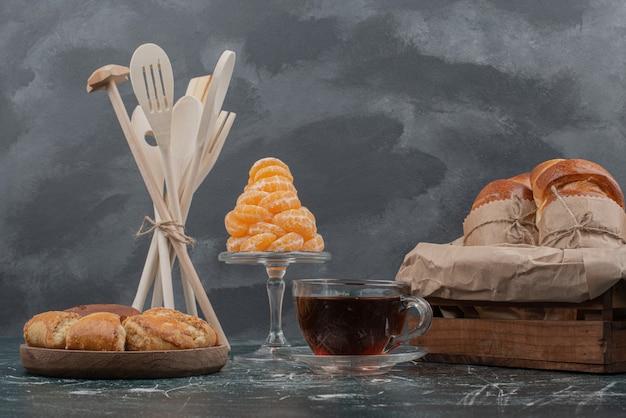 Plato de madera de panadería con utensilios de cocina en mármol.