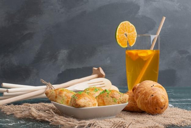 Plato de madera de panadería con utensilios de cocina sobre fondo de mármol.