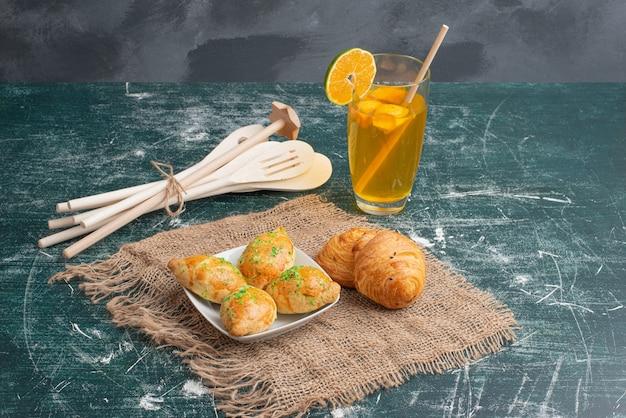 Plato de madera de panadería con utensilios de cocina sobre mesa de mármol.