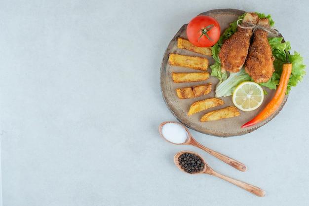 Un plato de madera de pollo frito y patatas.