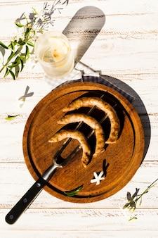 Plato de madera con salchichas a la parrilla sobre tenedor