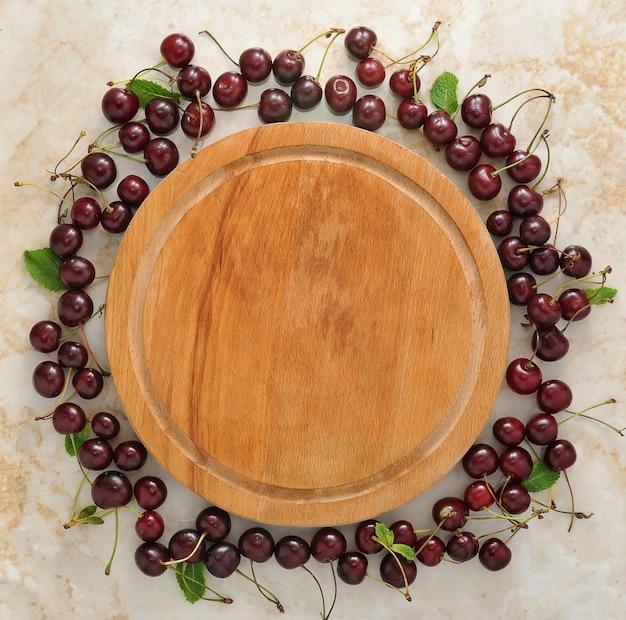 Plato de madera vacío y esparcido alrededor de cerezas