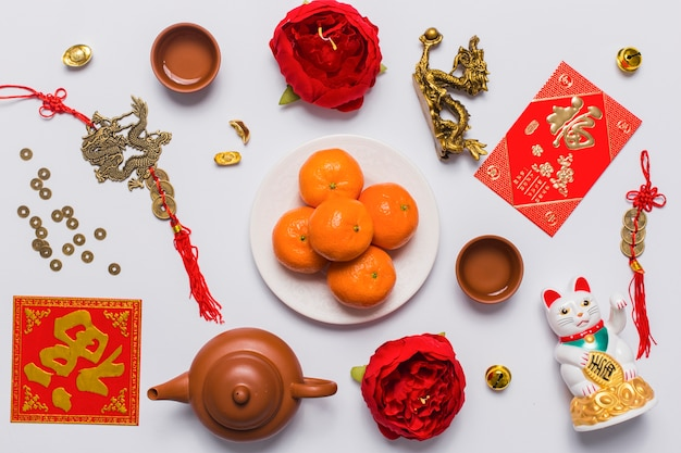 Plato con mandarinas en medio de cosas chinas