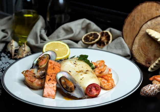 Plato de mariscos con salmón frito, mejillones, camarones, calamares y limón.