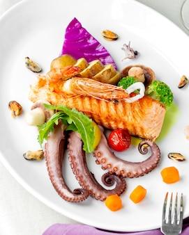 Plato de mariscos con salmón a la parrilla, pulpo, mejillones, camarones, champiñones y papas