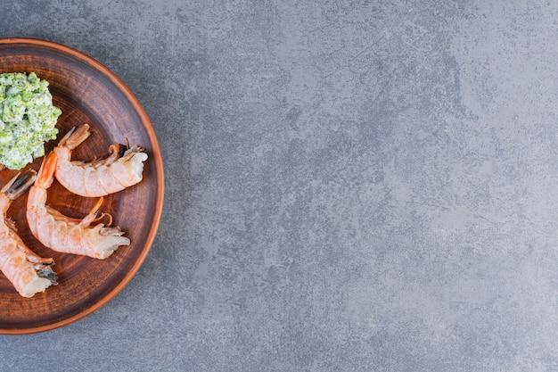 Un plato marrón de deliciosos camarones sobre una superficie de piedra