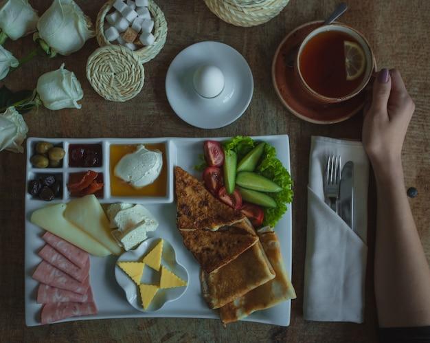 Plato del menú del desayuno con una gran selección de alimentos y una taza de té.