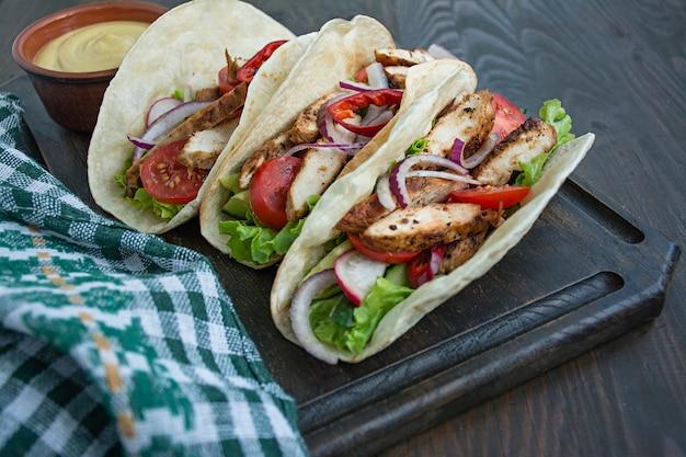Plato mexicano burrito envuelto con primer plano de pollo y verduras sobre un fondo de madera. espacio para texto.