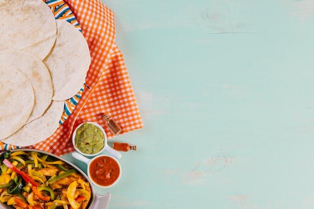 Plato mexicano cerca de tortillas y mantel