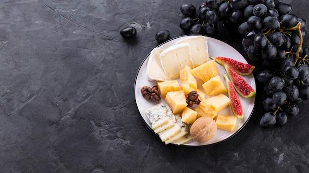 Plato de mezcla de queso con uvas negras