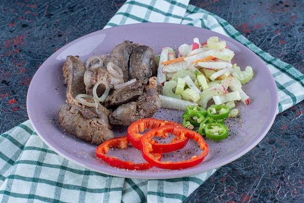 Un plato morado de deliciosa carne con verduras.