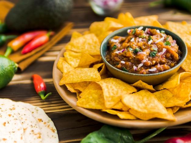Plato de nachos con salsa de salsa.