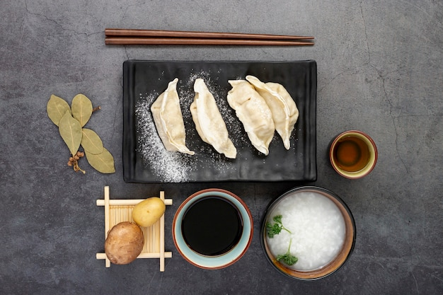 Plato negro de dim sum con tazón de sopa de arroz sobre un fondo gris