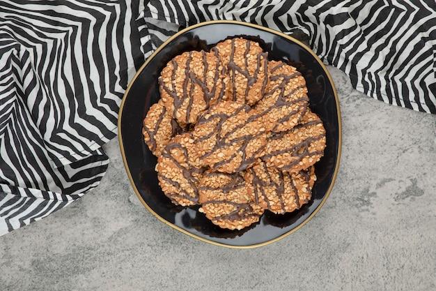 Un plato negro de galletas de avena con sirope de chocolate sobre una piedra.