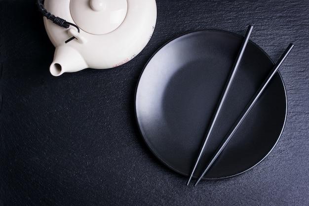 Plato negro con palillos chinos y una tetera