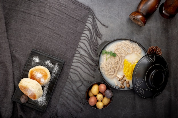 Plato negro con panqueques y un tazón con fideos