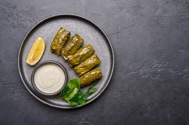Plato de oriente medio casero dolma o sarma con cacerola de perejil con crema agria y limón en negro